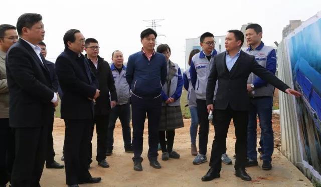 万鑫精工总经理周清泉(右二)向市委领导汇报二期工程情况